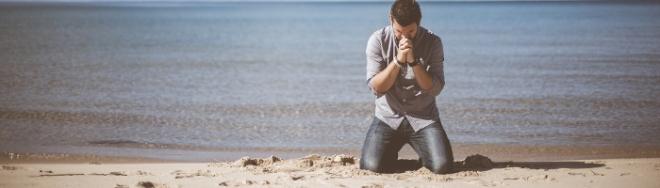 Hombre de rodillas orando en la playa