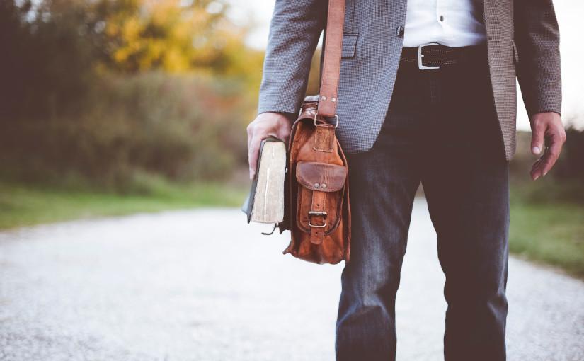 Hombre con Biblia y bolso en el camino