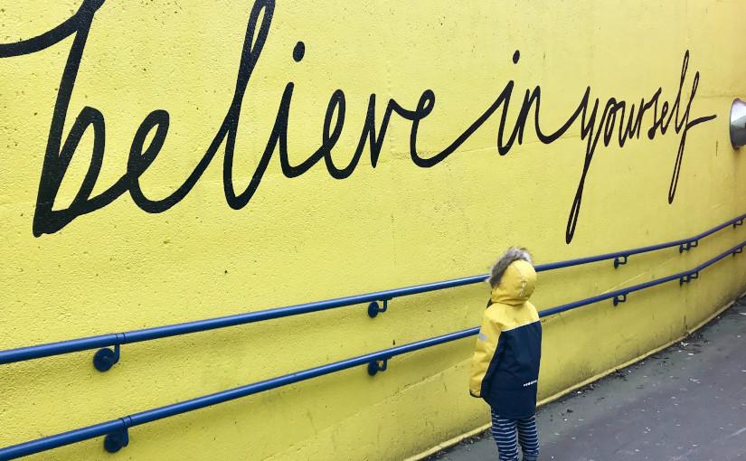 "Niño mirando a grafiti ""Cree en ti mismo"""
